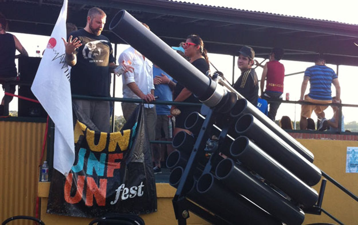 A man in a black shirt stands next to an enormous chambered tube gun with each barrel about the size of his head.